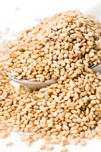 Heap of organic natural sesame seeds over white background.